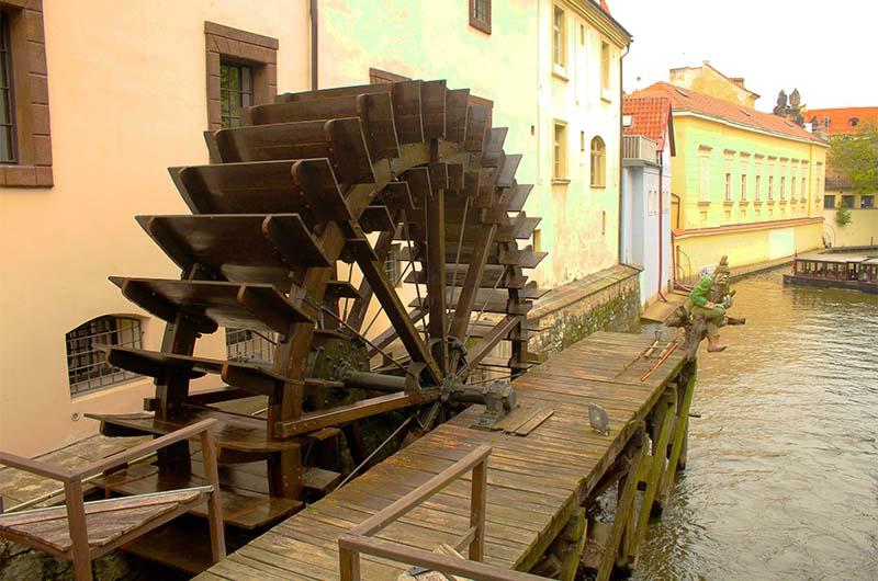 Колесо водяной мельницы рядом с мостом.