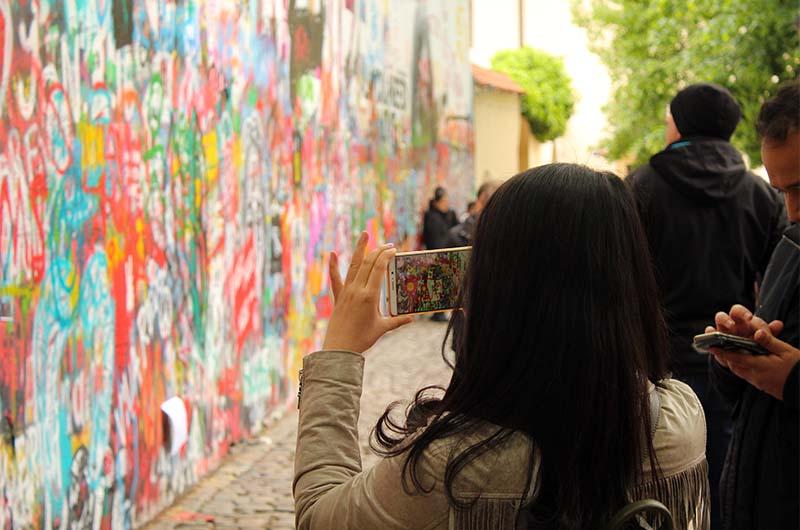 Люди ищут интересные фрагменты стены и фотографируют их на память.