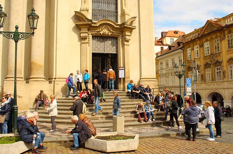 На ступенях главного входа в костёл сидят туристы, как будто студенты около университета.