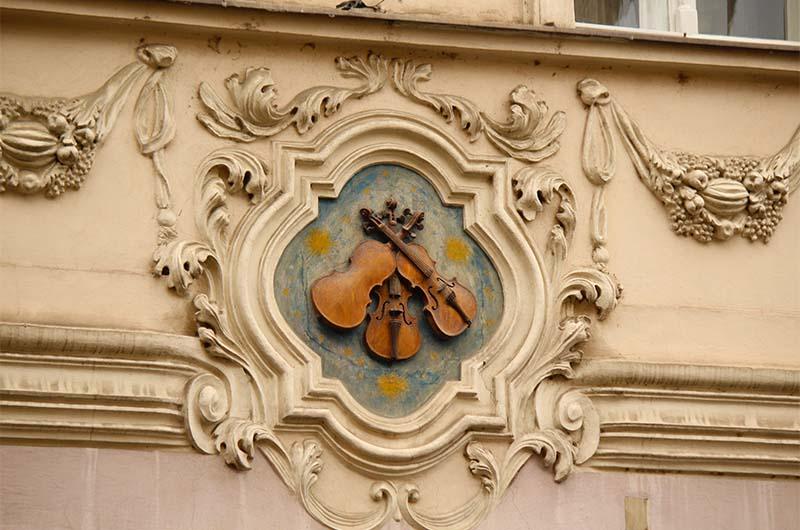 Раньше в Праге не было нумерации домов, и горожане отмечали свои домовладения вот такими «домовыми знаками». Знаки к тому же рассказывали и о владельцах дома. Например, этим домом «У трех скрипок» владели три поколения скрипачей. По легенде, на этих скрипках сейчас играют пражские привидения.