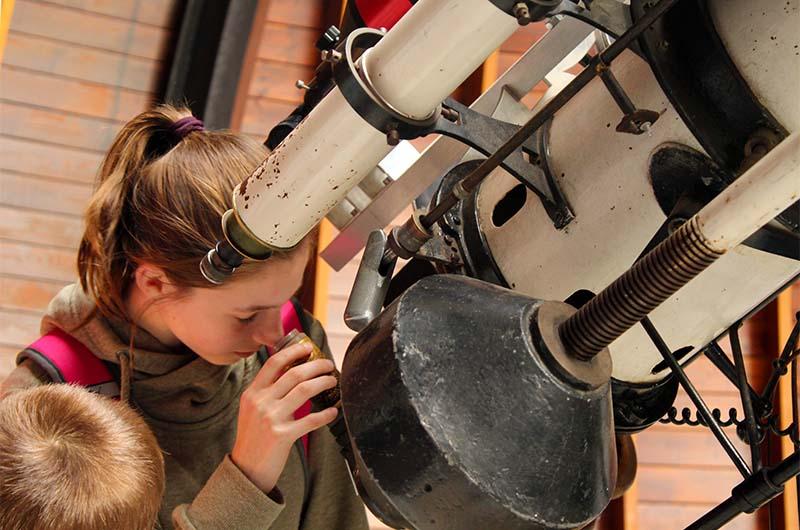 Девочка наблюдает за Солнцем в большой телескоп.