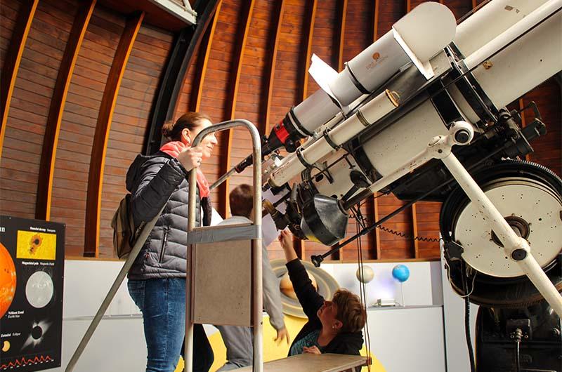 Чтобы посмотреть в большой телескоп, надо подняться по лестнице.